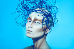 Attractive female with creative body art and hairstyle on blue b Stock Photos