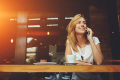 Attractive female with cute smile having talking conversation with mobile phone while rest in cafe Stock Photography
