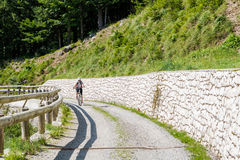 Attractive female cyclist tackling a steep road. Enjoying Madonna di Campiglio, Italy Royalty Free Stock Image