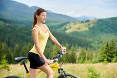 Attractive female cyclist with yellow mountain bicycle, enjoying sunny day in the mountains. Athlete happy woman cyclist riding on yellow mountain bike, enjoying stock photos