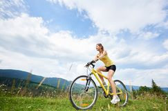 Attractive female cyclist with yellow mountain bicycle, enjoying sunny day in the mountains. Attractive happy woman cyclist riding on yellow mountain bicycle on royalty free stock image