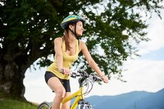 Attractive female cyclist with yellow mountain bicycle, enjoying sunny day in the mountains. Attractive happy woman cyclist riding on yellow mountain bicycle royalty free stock photo