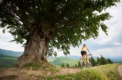 Attractive female cyclist with yellow mountain bicycle, enjoying sunny day in the mountains. Back view of athlete female cyclist cycling on yellow mountain bike stock images