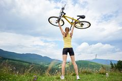 Attractive female cyclist with yellow mountain bicycle, enjoying sunny day in the mountains. Back view of athlete woman biker holding yellow mountain bicycle royalty free stock photo