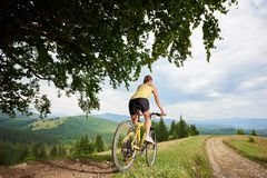 Attractive female cyclist with yellow mountain bicycle, enjoying sunny day in the mountains. Back view of attractive woman biker riding on yellow mountain stock photo