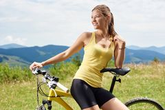Attractive female cyclist with yellow mountain bicycle, enjoying sunny day in the mountains. Portrait of athlete girl female cyclist sitting on yellow mountain stock photography