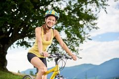 Attractive female cyclist with yellow mountain bicycle, enjoying sunny day in the mountains royalty free stock images