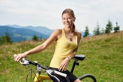 Attractive female cyclist with yellow mountain bicycle, enjoying sunny day in the mountains. Portrait of attractive happy woman biker with yellow mountain bike stock image