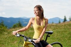 Attractive female cyclist with yellow mountain bicycle, enjoying sunny day in the mountains. Young happy female cyclist relaxing on yellow mountain bicycle royalty free stock image