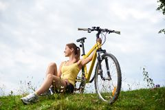 Attractive female cyclist with yellow mountain bicycle, enjoying sunny day in the mountains. Young happy woman biker sitting on a grassy hill with yellow royalty free stock photography