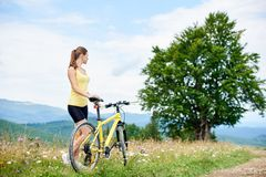 Attractive female cyclist with yellow mountain bicycle, enjoying sunny day in the mountains. Young happy woman biker standing with yellow mountain bicycle stock photography