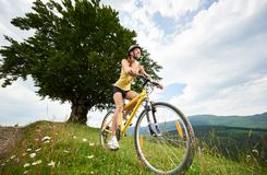 Attractive female cyclist with yellow mountain bicycle, enjoying sunny day in the mountains. Young happy woman cyclist riding on yellow mountain bicycle on a royalty free stock photo