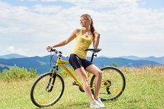 Attractive female cyclist with yellow mountain bicycle, enjoying sunny day in the mountains. Young happy woman cyclist sitting on yellow mountain bicycle royalty free stock photo