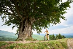 Attractive female cyclist with yellow mountain bicycle, enjoying sunny day in the mountains. Young happy woman cyclist riding on yellow mountain bicycle under stock photos