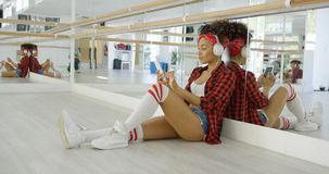 Attractive female dance student seated in studio Stock Image