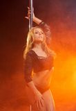 Attractive female dancer with dance pole Royalty Free Stock Image