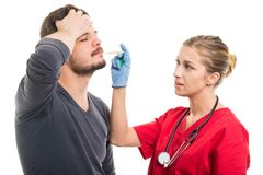 Attractive female doctor checking male patient temperature Stock Image