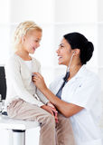 Attractive female doctor with her patient. Attractive female doctor checking her patient's ears in a medical practice Stock Image