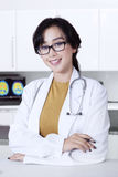 Attractive female doctor in hospital. Beautiful female asian doctor smiling at the camera while wearing glasses and uniform in the clinic Royalty Free Stock Photos