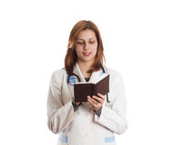 Attractive female doctor taking notes on a pad Stock Image