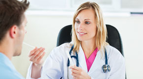 Attractive female doctor taking a saliva sample royalty free stock photos