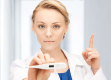 Attractive female doctor with thermometer. Picture of female doctor with thermometer showing finger up Royalty Free Stock Images