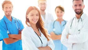 Attractive Female Doctor With Medical Stethoscope In Front Of Medical Group Stock Photo