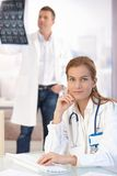 Attractive female doctor working on computer. Young attractive female doctor working on computer sitting at desk in office, smiling, male doctor in background Royalty Free Stock Photo
