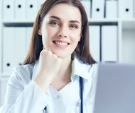 Attractive female doctor working on her laptop in her office. Happy doctor waiting for patient. royalty free stock photos