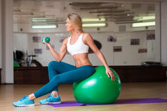 Attractive female doing dumbbell curls while Stock Photos