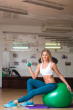 Attractive female doing dumbbell curls while Royalty Free Stock Photography