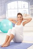 Attractive female doing exercises on floor Stock Images
