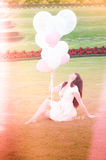 Attractive female dreaming with balloons. An attractive female in a park and dreaming with balloons Royalty Free Stock Image