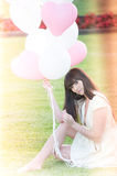 Attractive female dreaming with balloons. An attractive female in a park and dreaming with balloons Stock Photo
