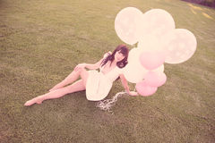 Attractive female dreaming with balloons. An attractive female in a park and dreaming with balloons Stock Image