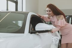 Young businesswoman shopping for new car at dealership showroom stock images