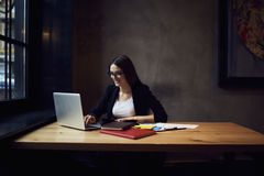 Attractive female editor of online issue in formal wear and trendy glasses. Making distance work sitting in modern interior office, smiling businesswoman royalty free stock image