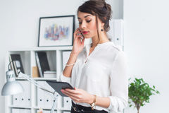 Attractive female employee speaking on the phone, having negotiations, using mobile phone and tablet in office. Royalty Free Stock Photo