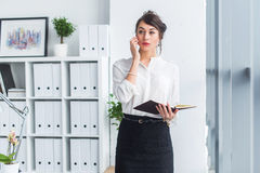 Attractive female employee speaking on the phone, having negotiations, using mobile and tablet in office. Attractive female employee speaking on the phone royalty free stock images
