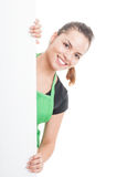 Attractive female employee standing behind blank banner Royalty Free Stock Photography