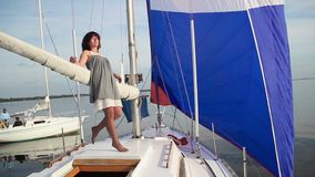 Attractive female enjoying summer vacation on sailing yacht. Stock footage stock footage