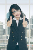Attractive female entrepreneur shows thumbs up Stock Photography