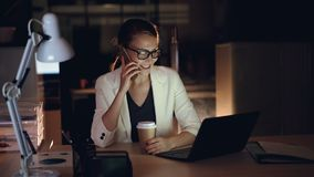 Attractive female entrepreneur is talking on mobile phone and using laptop working in office late at night. Modern