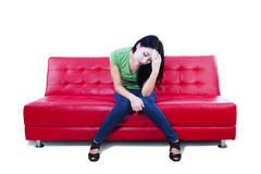 Attractive female feel depressed on red sofa - isolated Stock Image