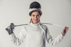Attractive female fencer. In protective clothing is holding a weapon, looking at camera and smiling, on gray background Royalty Free Stock Images