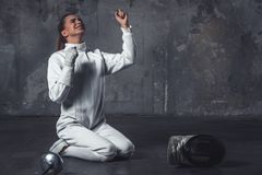 Attractive female fencer. In protective clothing is sitting on her knees and screaming with happiness, on dark gray background Stock Photography