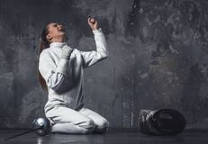 Attractive female fencer. In protective clothing is sitting on her knees and screaming with happiness, on dark gray background Stock Image
