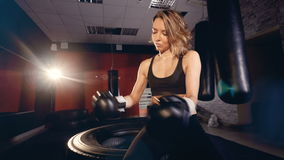 Attractive female fighter putting on boxing gloves in fitness studio. stock video