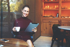 Attractive female freelancer holding touch pad and smiling for the camera while resting in cozy cafe Royalty Free Stock Photos
