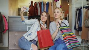 Attractive female friends are using smartphone to make selfie while sitting in clothing shop with colourful paper bags. Attractive female friends are using stock video footage